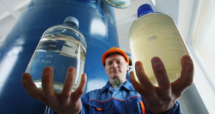 Сотрудник Водоканала демонстрирует воду до и после очистки на станции