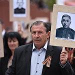 Цхинвальцы пронесли портреты своих погибших на войне родственников