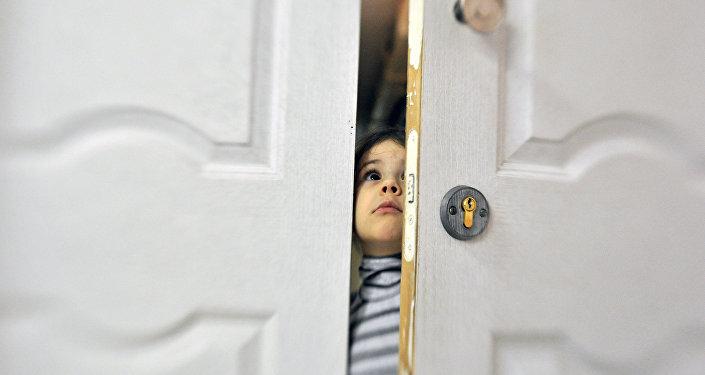 Девочка заглядывает в приоткрытую дверь социального отделения городской детской больницы