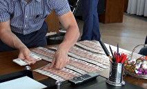 Сотрудник правоохранительных органов раскладывает деньги на столе в кабинете директора банка