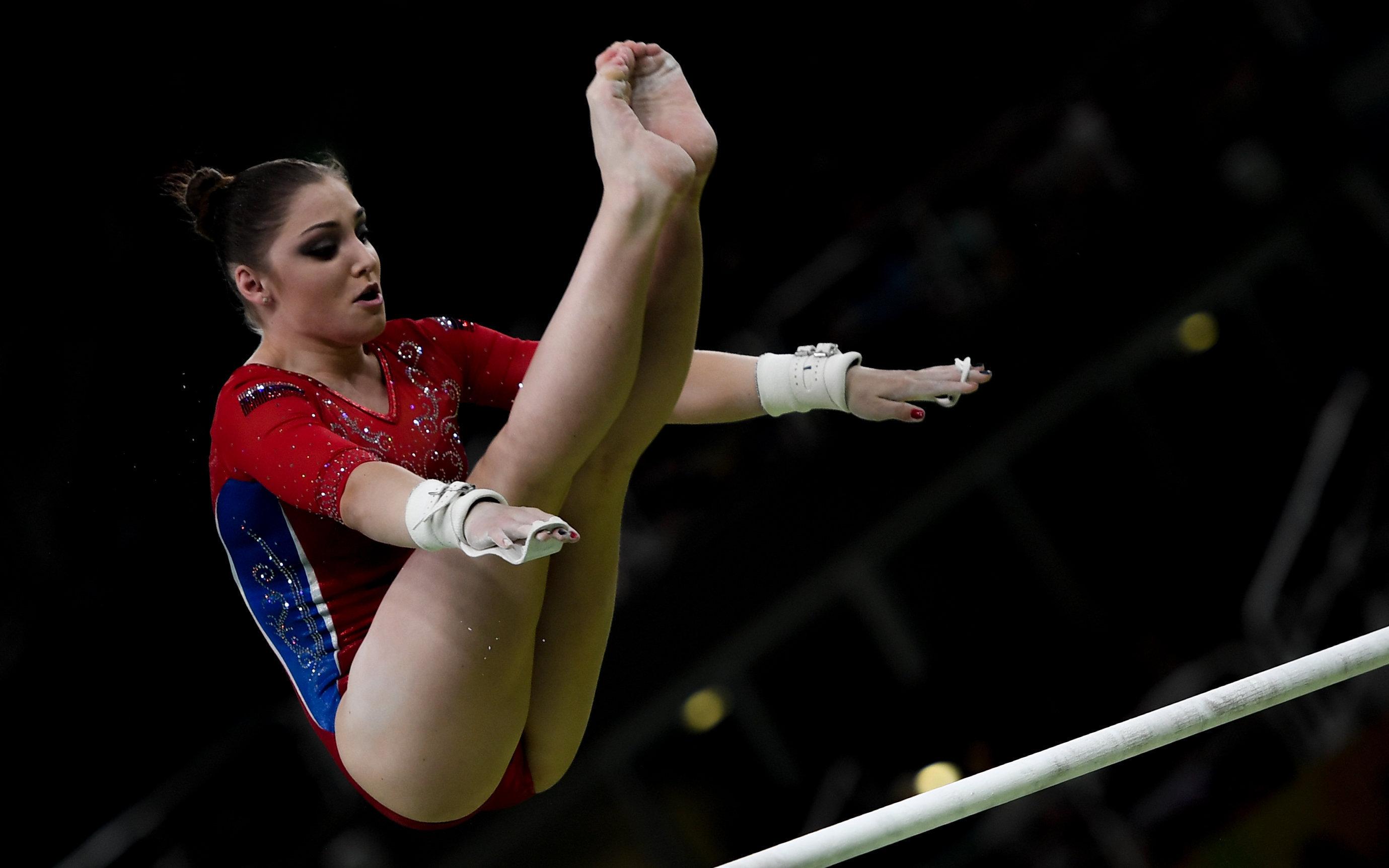 Алия Мустафина (Россия) выполняет упражнения на разновысоких брусьях