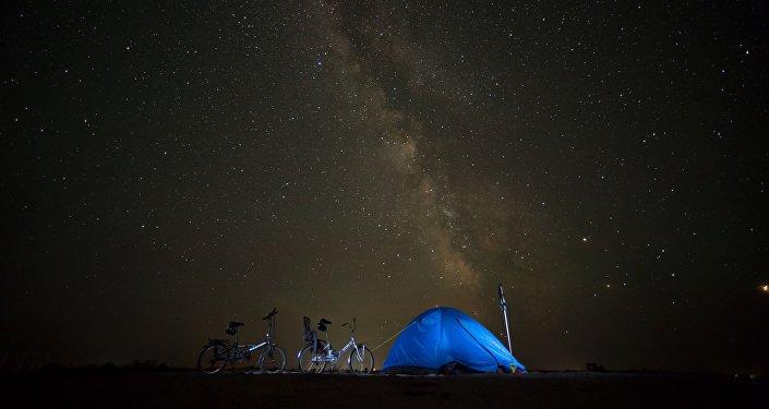 Палатка велотуристов на фоне ночного неба