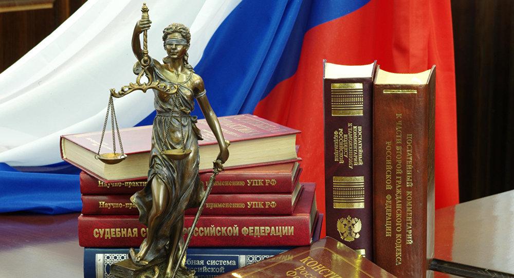 Статуя Фемиды и юридическая литература на столе в зале судебных заседаний