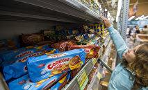 Девушка выбирает еду в магазине
