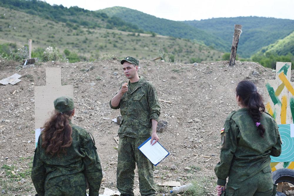Руководитель подводит курсанта к мишени и указывает на допущенные промахи, отмечая попадание.