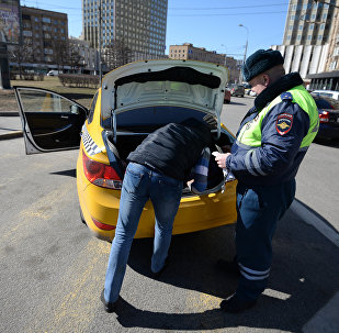 Сотрудник ГИБДД проверяет документы у таксиста