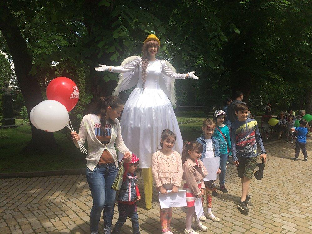В центральном парке гостей праздника встречала дама на ходулях