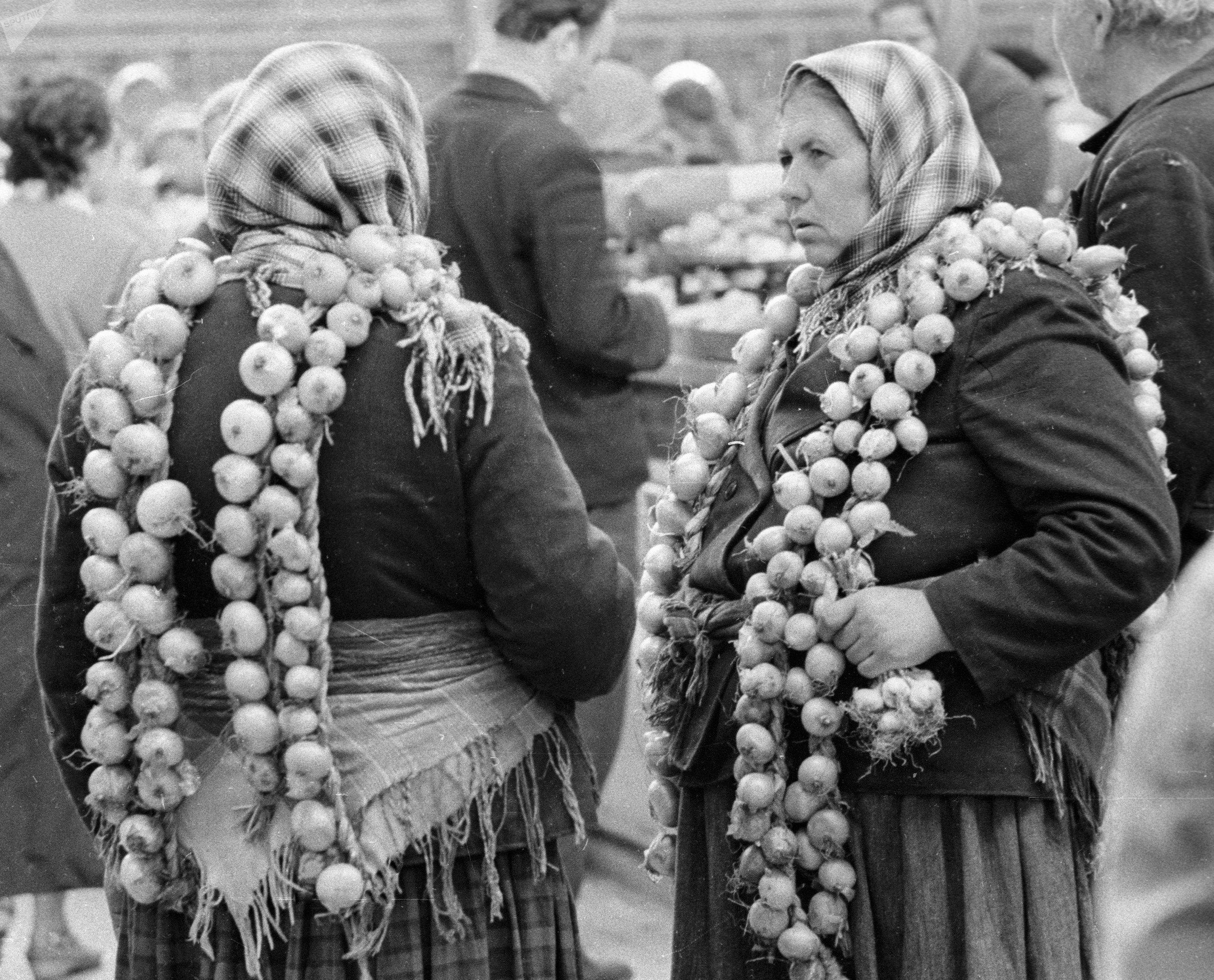 Женщины продают на рынке связки лука