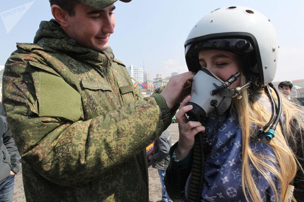 Военнослужащий помогает девушке примерить летный шлем на выставке боевой техники на центральной площади Владивостока