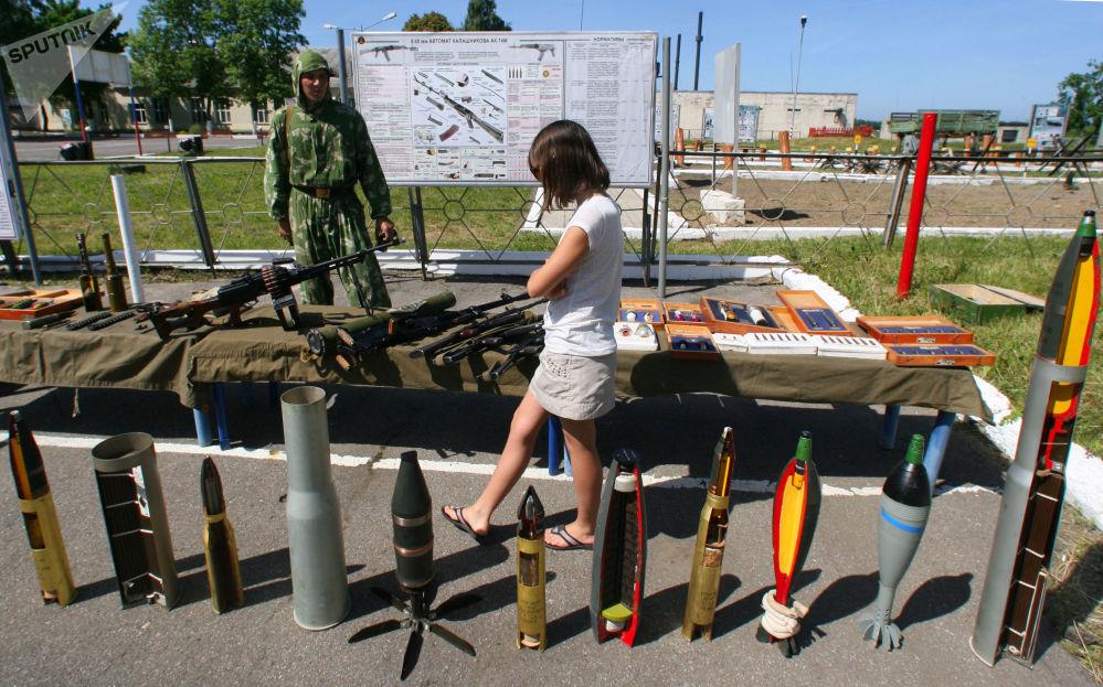 Девушка осматривает образцы снарядов, мин, гранат и других взрывных устройств во время Дня открытых дверей в морском инженерном батальоне Балтийского флота