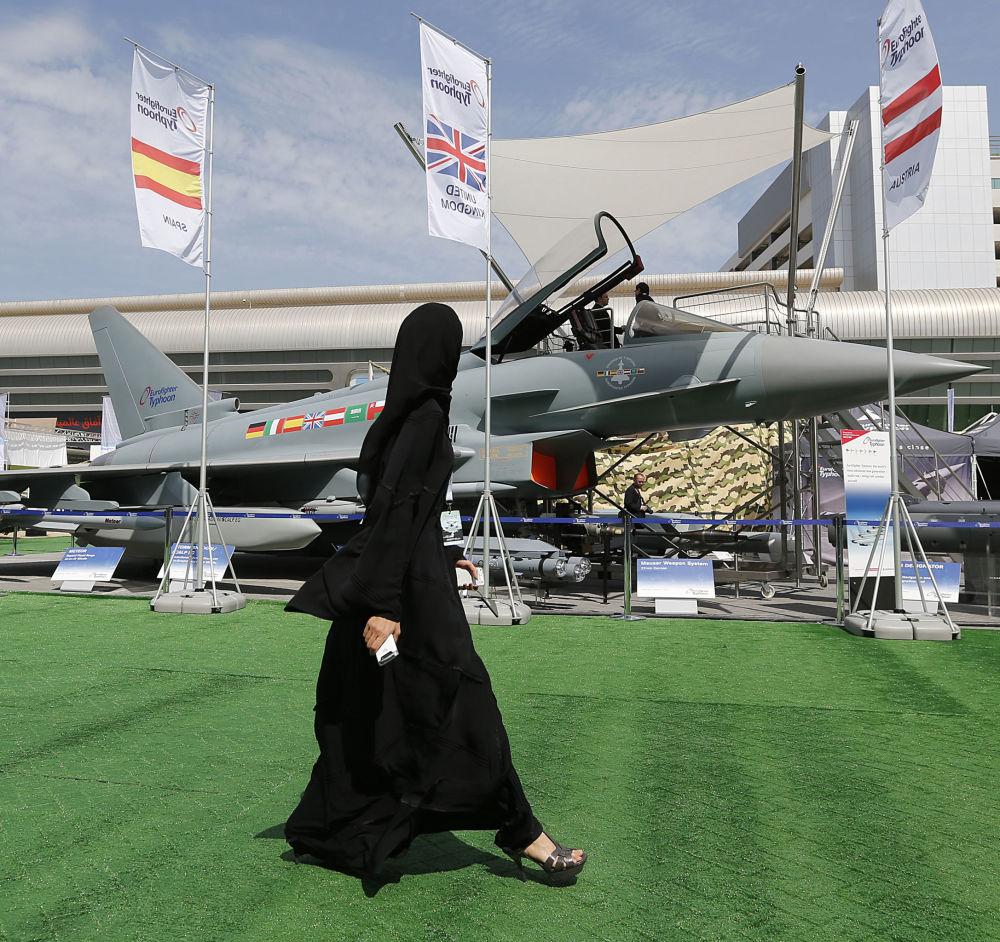 Девушка проходит мимо истребителя Eurofighter Typhoon на выставке IDEX в ОАЭ