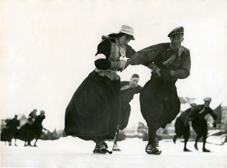 Катание на деревянных коньках в традиционных костюмах в Маркене, Нидерланды. 1938 год Архивное фото