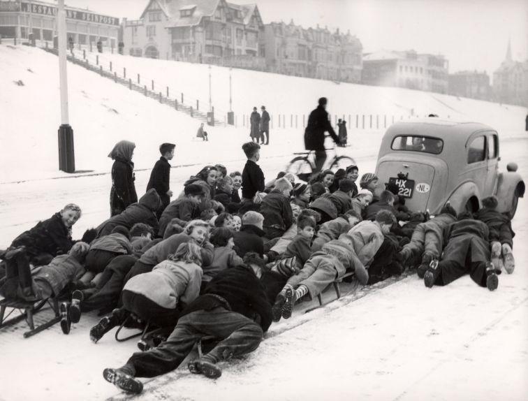 Автомобиль катает детей на санях на заснеженной дороге в Схевенингене, Нидерланды. Архивное фото