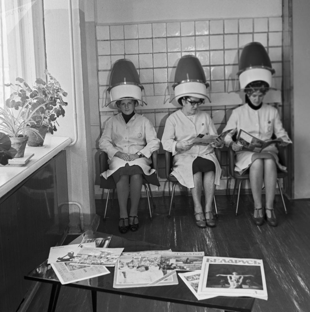 Женщины сидят в парикмахерской под сушилками для волос, 1980 год
