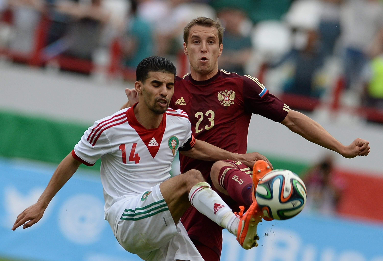 Бывший игрок Локомотива Мубарак Буссуфа и полузащитник Спартака Дмитрий Комбаров в ходе товарищеской встречи национальных сборных в 2014 году.