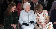 Королева Елизавета II на показе Недели моды в Лондоне, справа от нее - глава Британского модного совета Каролин Раш, слева - шеф-редактор Vogue Анна Винтур