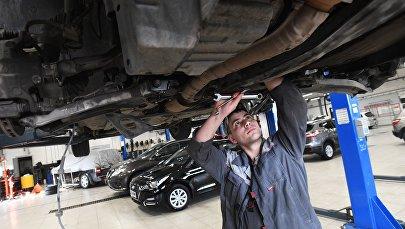 Сотрудник сервисного центра осматривает автомобиль