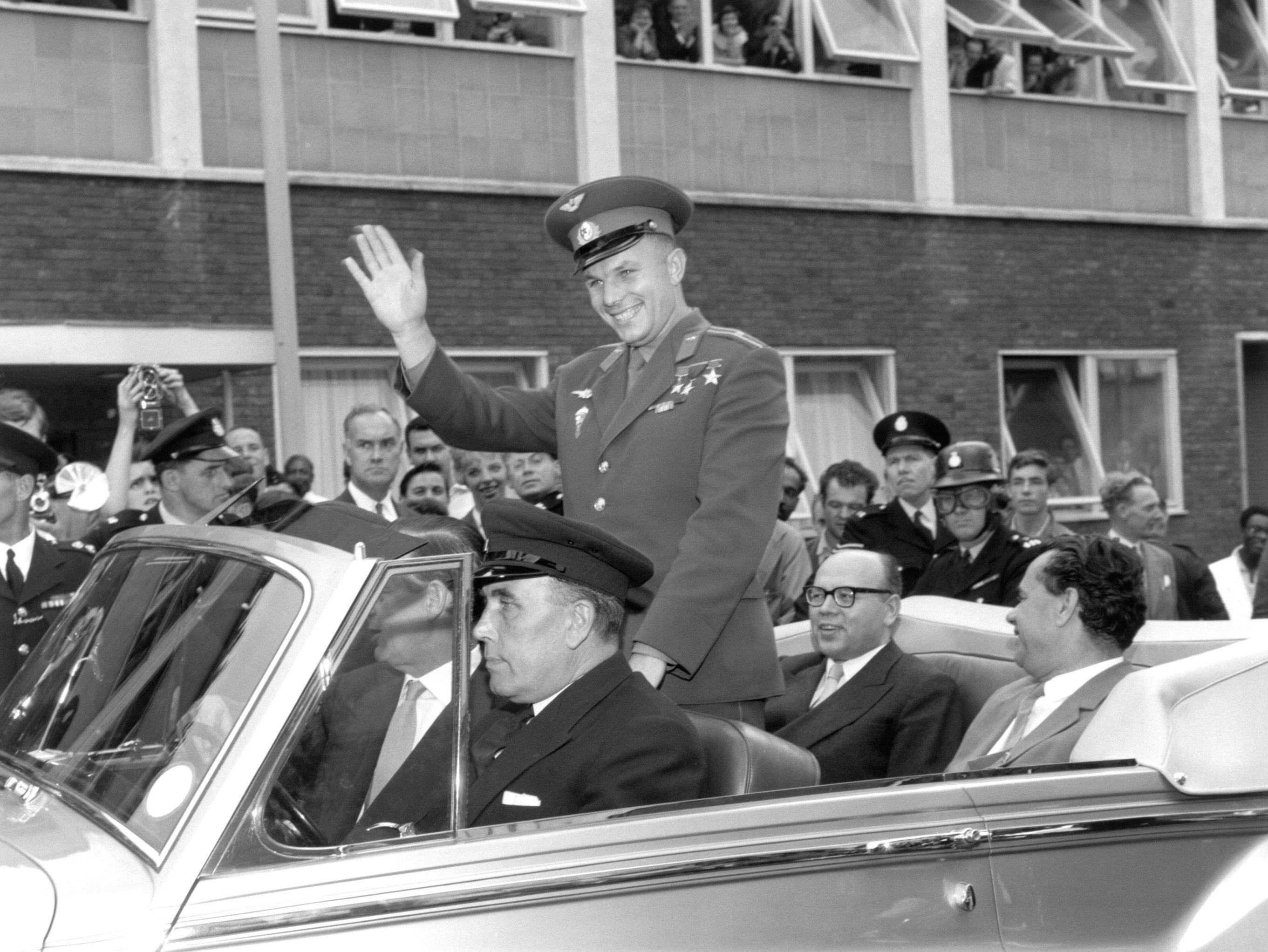 Юрий Гагарин (1934-1968), советский космонавт и первый человек в космосе, едет по Лондону в открытом автомобиле.