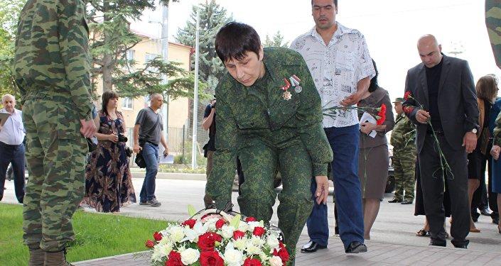 Президент фонда раненных Мадина Плиева возлагает цветы к мемориалу погибших в августе 2008 защитников РЮО